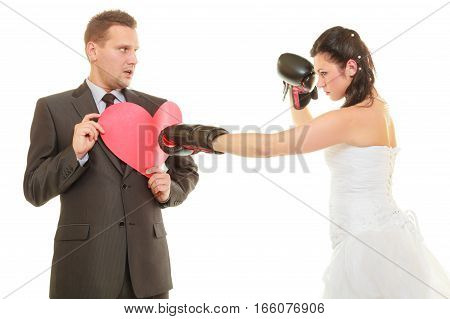 Conflict in relationship concept. Married couple fighting with each other. Woman wearing wedding dress and boxing gloves punching her husband in suit holding heart.