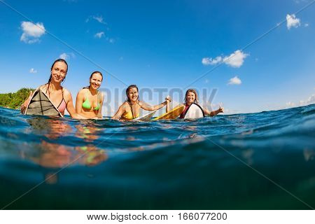 Happy girls in bikini have fun - group of surfers sit on surf boards young women wait for big ocean wave. People in water sport adventure camp beach extreme activity on summer beach family vacation