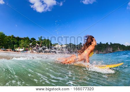 Girl in bikini has fun on surf board - woman surfer run into water jump with splashes through ocean wave. People in water sport adventure camp beach extreme activity on summer beach family vacation.