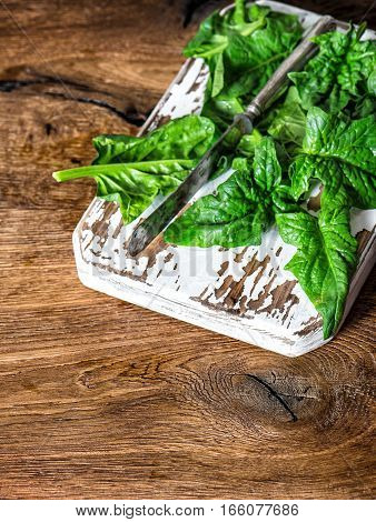 Fresh green spinach leaves on rustic wooden background. Healthy organic food