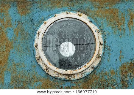 Porthole on the blue wall of the old ship. Stock image.