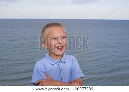 Close up portrait of laughing blond boy outdoors.