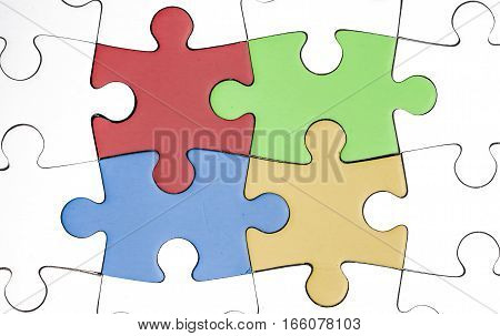 white jigsaw with four colored pieces in the middle. teamwork solidarity human hope
