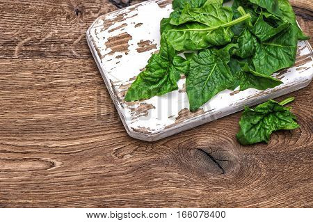 Fresh green spinach on rustic kitchen background. Healthy organic food