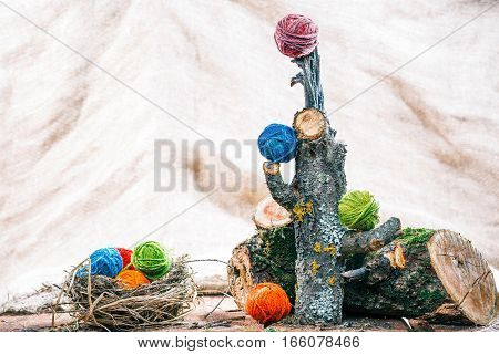 Colorful yarn balls in a nest and on natural raw logs