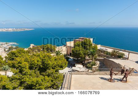 Alicante, Spain- September 9, 2016: Mediterranean and Spanish coastline view from atop Castell Santa Barbara with bright blue of sea to horiizon and green trees over upper castle decks with sparring medieval soldiers sculpture Alicante Spain