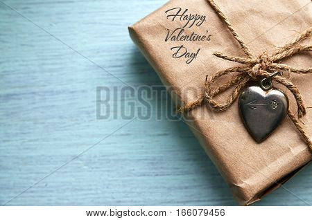 Valentines Day gift with silver heart on a blue wooden background.Happy Valentine's Day background.Saint Valentine's Day or Love concept.Selective focus.