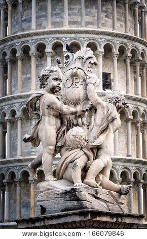 Statue of cherubs holding a shield with the Cross of Pisa on it in Pisa Italy