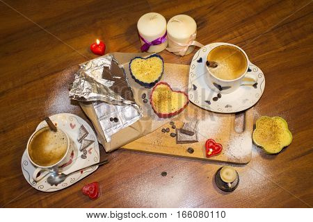Two beautiful cups of cappuccino coffee with candles and chocolate for lovers in romantic atmosphere