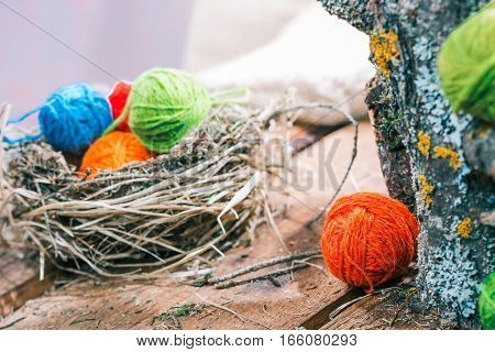 Colorful wool balls in bird nest and next to raw logs on wooden boards