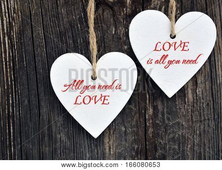 All You Need Is Love.Decorative white wooden hearts on old wooden background.Two Valentine hearts.Valentine's Day or Love concept.Selective focus.