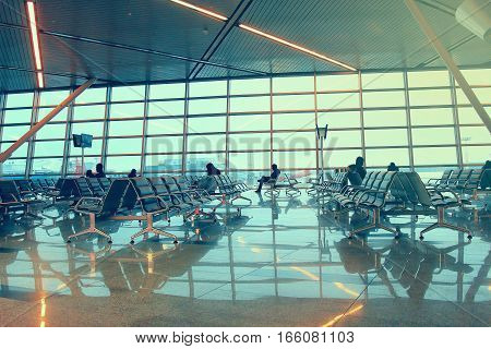Silhouettes of people traveling on airport waiting at the plane boarding gates.
