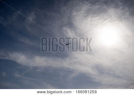 Helicopter in the blue sky. Sun and cloud.