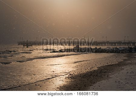 Gdynia Orlowo. Winter morning - beach pier it's snowing and the sun is shining at the same time.