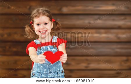 happy laughing child girl with heart Valentine's Day wooden background