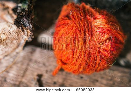Red wool ball on wood table near natural log. Macro view