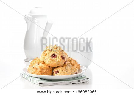 Fresh lemon cranberry scones with a coffee pot and cups in the background.