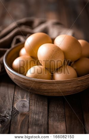 fresh brown eggs on wooden background closeup