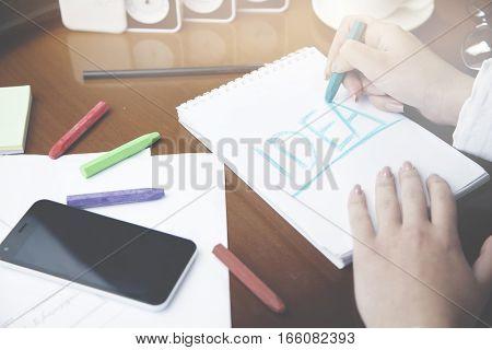 woman writing idea on notebookpencilcoffeeglasses on table