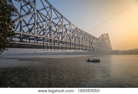 Howrah bridge Kolkata at dawn with wooden boat on river Hooghly.