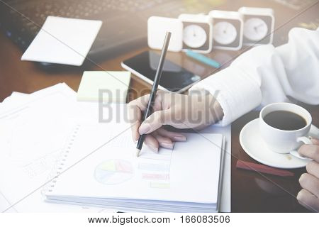 woman writing pencil on notebook on wooden table