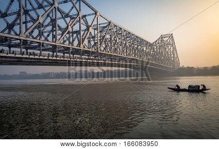 Historic Howrah bridge on Ganga river on a misty winter morning with a wooden fishing boat passing the bridge. Kolkata, India.