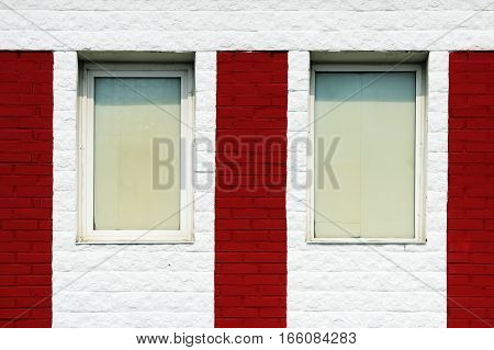 texture of bright red brick wall with white stripes and windows on a sunny day