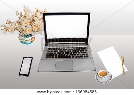 Workplace with laptop white screen, smart phone, white blank paper and pen with morning tea isolated.