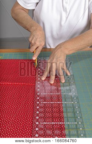 A quilter uses a rotary cutter to cut fabric for a quilt.