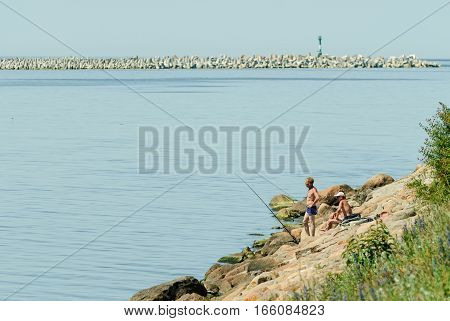 Baltiysk, Russia - June 29, 2010: Sea fishing - fishermen catch a sprat from the Northern pier in sunny day