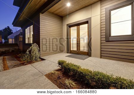 New Construction Home With Low Slope Roof And Brown Siding.