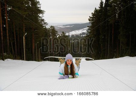 Smiling woman with snowboard in the ski resort