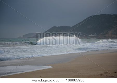 Seascape with with dramatic wave splash and turquoise water during storm on beautiful Cleopatra beach famous for it sand in Alanya Turkey in winter on gloomy day with Taurus Mountains as background