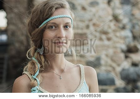Close up portrait of beautiful blonde girl with blue eyes and braid wearing blue earrings and turquoise headband against blurred background of stone wall