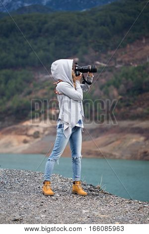 Full length portrait of young woman photographing landscape using long range lens and dressed in grey hood jeans and boots of ocher color with river and mountains covered with pine forests on background