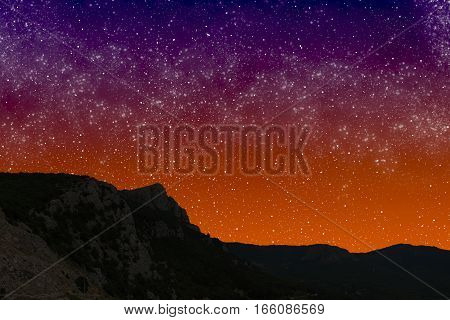Mountains at night on the background of starry sunset sky.
