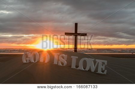 White 3D words that say God is love on a sandy beach at sunset.