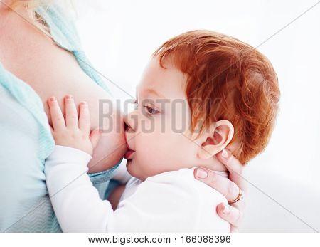 mother breastfeeding her adorable ginger baby, bonding concept