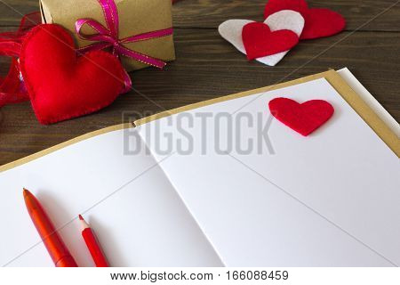 notebook with pen and pencil, the heart of felt and a gift in the background on the table