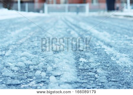 road after thaw and frost covered with slippery ice icy