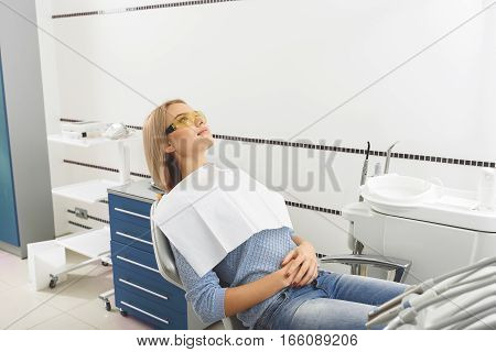Serene woman in anticipation of oral surgeon. She sitting with crossing arms on a dentist chair in stomatological room. Instruments are around patient