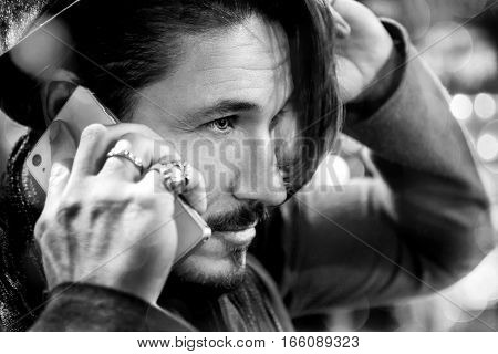 Man talking on the phone on the street. Black and white photo.