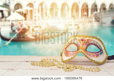 Carnival mask over blurred venetian background with gondola boat
