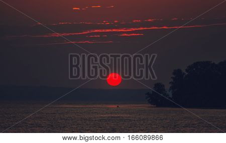 Beautiful romantic sunset on the background of cloudy sky and sea.