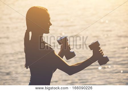 Beautiful athlete involved in sports on the street conducts training with dumbbells in his hands. The concept of a healthy lifestyle and sports culture.