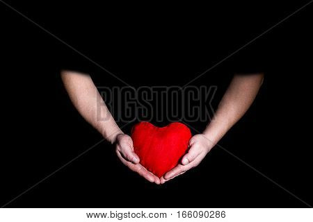 male hands holding a heart on a black background Valentine's Day