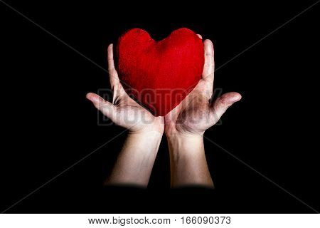 in the men's hands lies the heart on a black background Valentine's Day