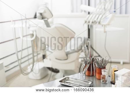 Dental treatment unit being in briht white room of stomatologist. Focus on table with tools of dentist