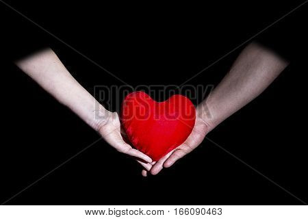Male and female hands holding a heart on a black background Valentine's Day