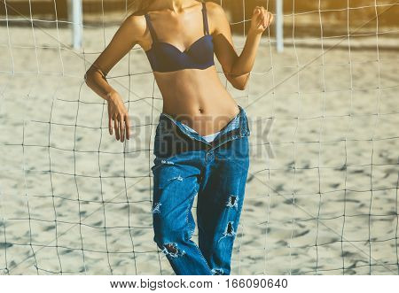 Young attractive girl in a black cap jeans with holes and a bra on a beach near the net for football. The rebellious style.